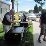 Lions Jim Trupp, Harold Einarsen, and Dale Edwards are getting the grills ready to cook.