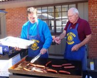 Brian White and Bob McLean are grilling the hot dogs.